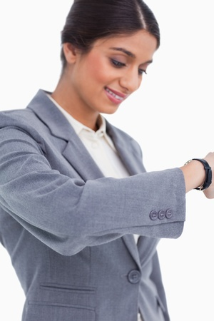 Close up of female entrepreneur looking at watch against a white background photo