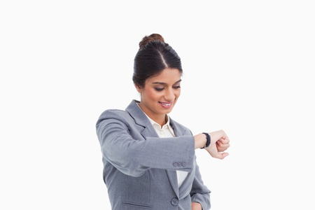 Smiling female entrepreneur looking at her watch against a white background Stock Photo - 13653533