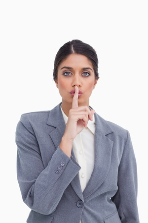Close up of female entrepreneur asking for silence against a white background photo