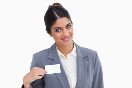 Smiling female entrepreneur pointing at name sign against a white background photo