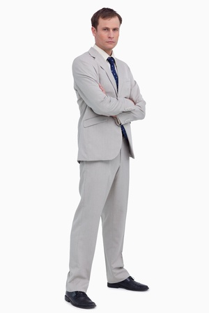 Serious businessman standing with his arms folded against a white background photo
