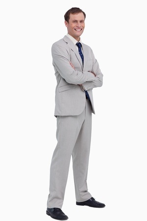 Smiling businessman standing with his arms folded against a white background photo
