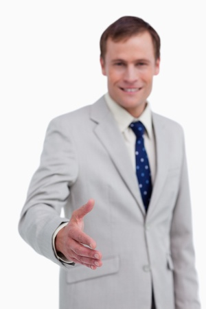 Hand being offered by smiling businessman against a white background photo