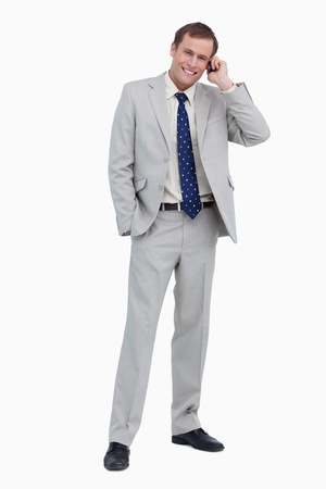 Smiling businessman on his mobile phone against a white background photo