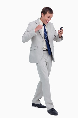 Happy businessman getting good news via text message against a white background photo