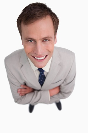 Close up of smiling businessman with his arms folded against a white background photo