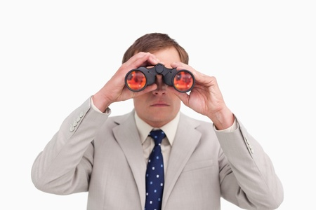 Businessman using binoculars against a white background photo