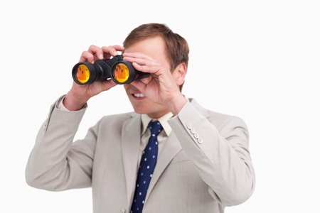 Businessman using spy glasses against a white background photo