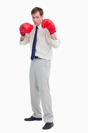 Businessman with his boxing gloves ready to fight against a white background photo