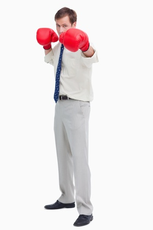 Businessman with boxing gloves in offensive position against a white background Stock Photo - 13673636