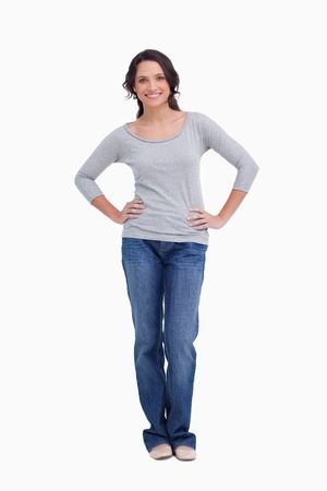 arms akimbo: Smiling woman with hands on her hip against a white background Stock Photo