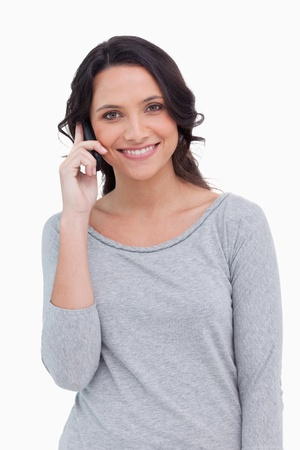 Close  up of smiling woman on her cellphone against a white background photo