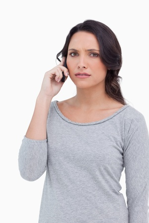 Close up of woman on her mobile phone against a white background photo