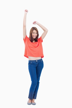 arms above head: Casual teenager smiling and raising her arms above her head