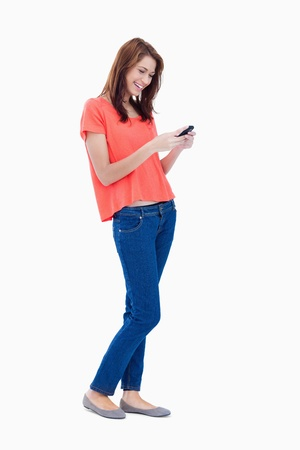 looking away: Laughing adolescent sending a text with her mobile phone