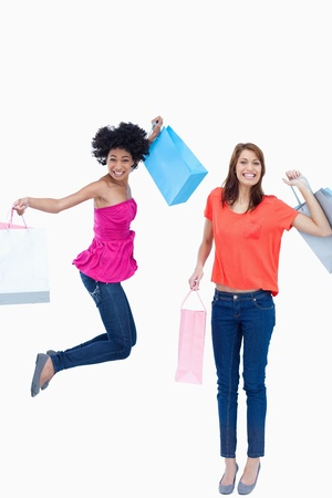 A teenage girl leaping while holding her shopping bags while her friend is smiling photo