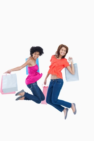 Dynamic teenagers energetically leaping after going shopping photo