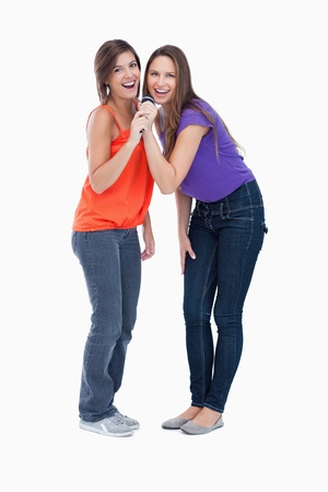 Smiling teenagers singing in a cordless microphone Stock Photo - 13675056