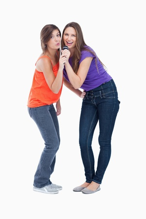 Two smiling teenagers naturally bending their bodies while singing Stock Photo - 13675059