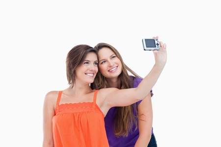 Beaming teenager taking a photo of herself and a smiling friend Stock Photo - 13675098