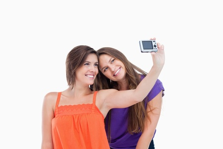 Smiling teenager laying her head on her friend's shoulder against a white background Stock Photo - 13675077