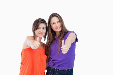 Smiling teenagers putting their thumbs up against a white background photo