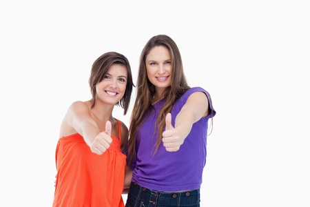 Happy teenagers giving the thumbs up for agreement Stock Photo - 13675090