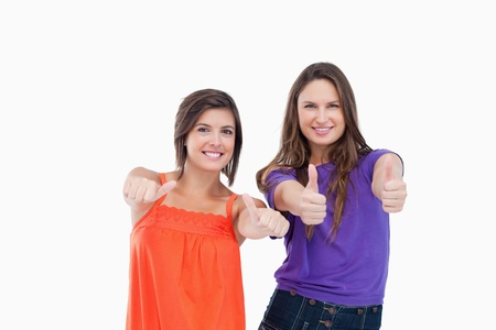 Smiling teenager standing up with her thumbs turned to the side while her friend puts her's up Stock Photo - 13675053