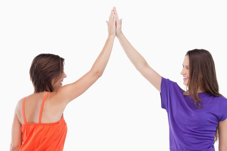 Two friends joining their hands in the air against a white background Stock Photo - 13675105