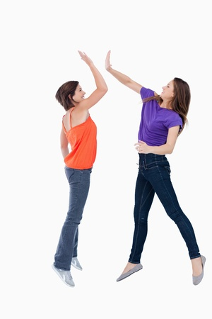 Smiling teenagers jumping while trying to high-five each other in the air Stock Photo - 13675141