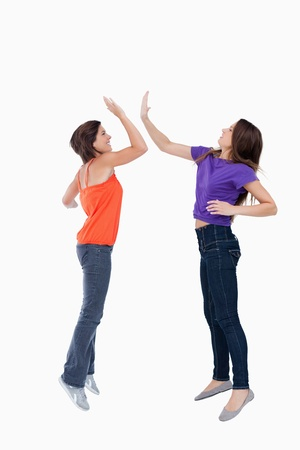 Smiling and dynamic teenagers jumping while giving a high-five Stock Photo - 13675158