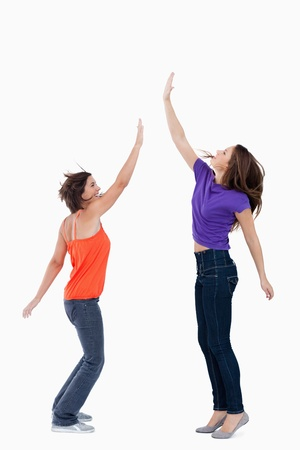 Smiling teenager standing on the tips of her toes while her friend is trying to touch her hand Stock Photo - 13675155