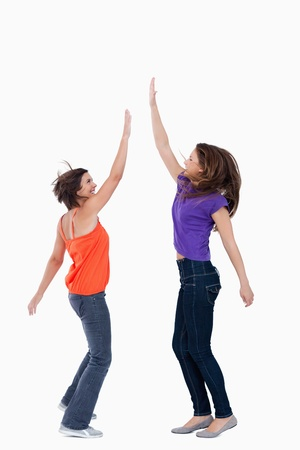 Smiling teenager keeping her hand in the air while her friend tries to touch it Stock Photo - 13674632