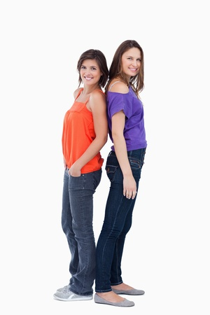 Adolescents standing back to back in front of a white background Stock Photo - 13674261