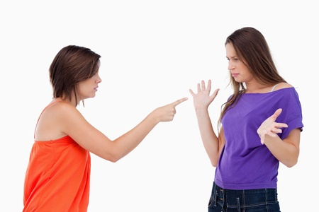 accusing: Teenage girl accusing her friend by pointing at her with her finger