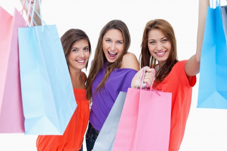 Happy teenagers raising their arms while holding their purchase bags photo