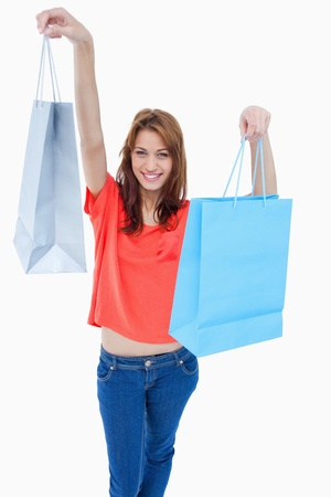 Teenage raising her shopping bags in the air while smiling photo