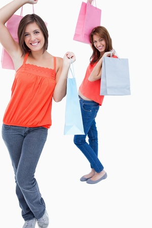 Teenager followed by a friend and both are holding shopping bags while smiling photo