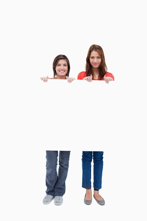 Smiling teenagers proudly holding a blank poster against a white background photo