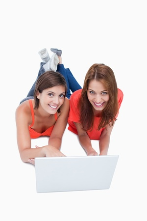 Teenagers crossing their legs while lying down behind a laptop Stock Photo - 13676199