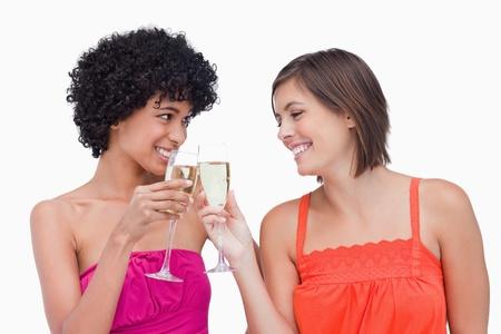 clinking: Adolescentes sonrientes chocando copas de champ�n Foto de archivo