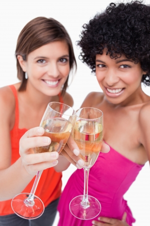 Two glasses of white wine being clinked by young women Stock Photo - 13679165