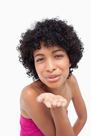 Smiling woman sending a kiss against a white background photo