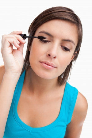 Teenager almost closing her eyes while applying black mascara photo