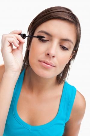 eyes closing: Teenager almost closing her eyes while applying black mascara Stock Photo