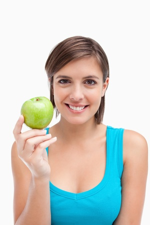 Young woman holding a green apple in her right hand against a white background photo