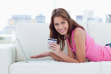 Young woman showing a beaming smile while holding a grey credit card Stock Photo - 13677910