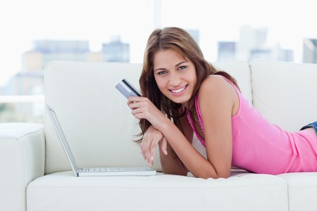 Young woman lying on a sofa in front of her laptop holding her credit card Stock Photo - 13677684