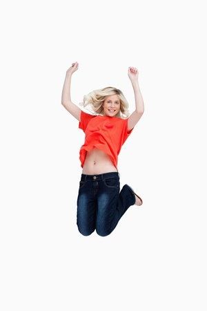 arms above head: Fair-haired teenager energetically jumping and raising her arms above the head