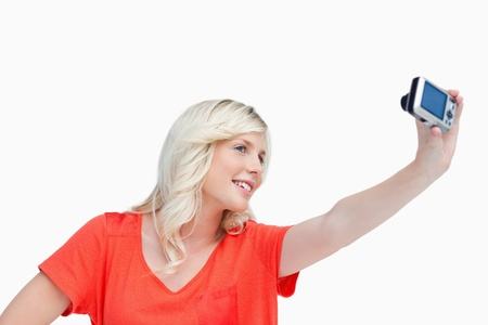 Smiling teenager photographing herself against a white background photo